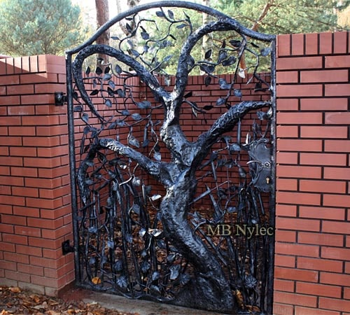 Openwork wrought iron gate with a forged tree