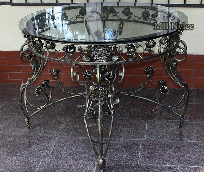 A large forged rose table with a glass top
